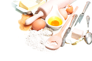Baking ingredients eggs, flour, sugar, butter, yeast. Food background with antique cutlery
