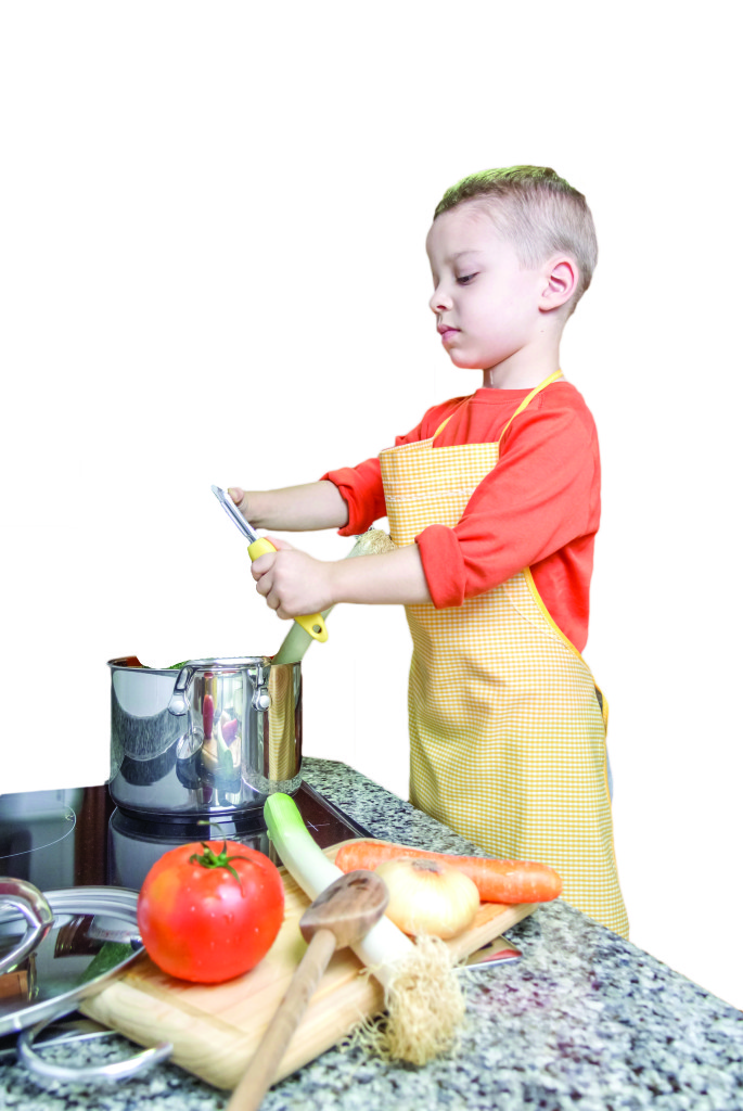 Cute child chef with apron cooking big zucchini and other vegetables in a pot on the kitchen